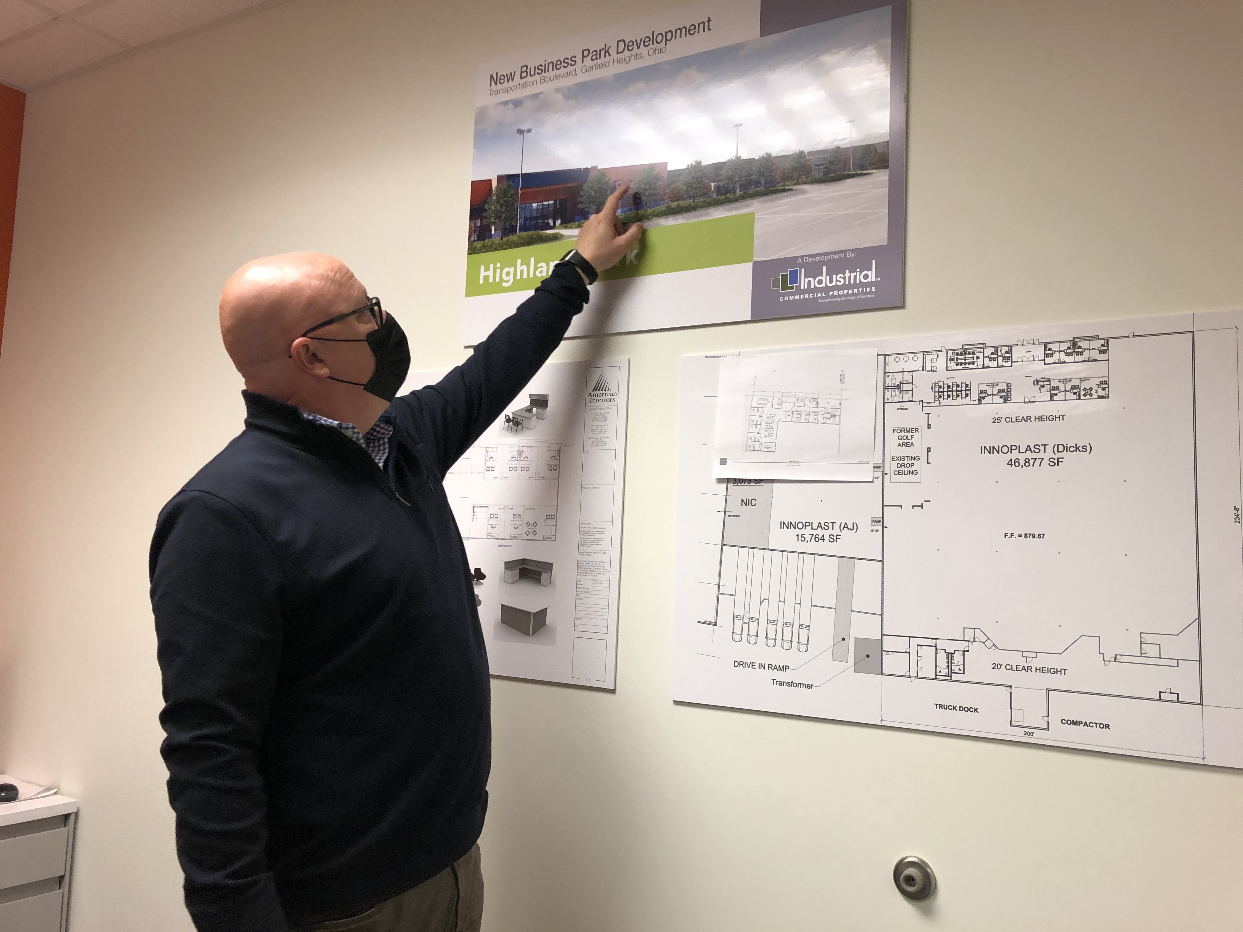 Gary Bowling pointing out the location of the new Innoplast headquarters on a digital rendering.